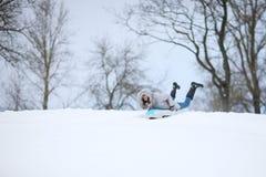 Funny woman sledding on a tube Stock Photo