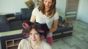 Funny woman smile while her girlfrind make fun curler hairstyle stock video