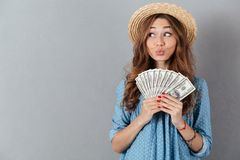 Funny woman standing over grey wall wearing hat holding money. Image of young funny woman standing over grey wall wearing hat holding money. Looking aside Stock Images