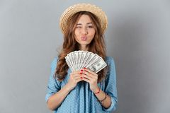 Funny woman standing over grey wall wearing hat holding money. Picture of young funny woman standing over grey wall wearing hat holding money. Looking camera Stock Photos