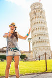 Funny woman supporting leaning tower of pisa Stock Photos