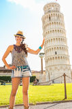 Funny woman supporting leaning tower of pisa Stock Image