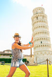 Funny woman supporting leaning tower of pisa Stock Photo