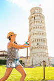 Funny woman supporting leaning tower of pisa Royalty Free Stock Image