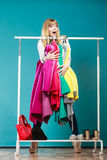 Funny woman taking all clothes in mall or wardrobe Royalty Free Stock Image