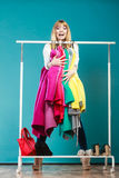 Funny woman taking all clothes in mall or wardrobe Royalty Free Stock Images