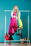 Funny woman taking all clothes in mall or wardrobe Stock Photography