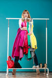 Funny woman taking all clothes in mall or wardrobe Stock Photos
