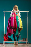 Funny woman taking all clothes in mall or wardrobe Royalty Free Stock Photography