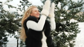 Funny woman throw snow up in pine winter snowy forest outdoors. stock video footage