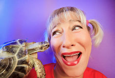 Funny woman with tortoise portraitn. Funny woman with tortoise on vivid color background Royalty Free Stock Photos