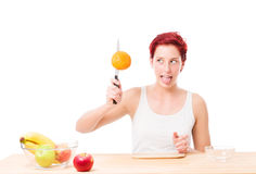 Funny woman trying to cut a orange Royalty Free Stock Images