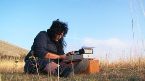 Funny Woman Typing On Vintage Typewriter Sitting. This is a low angle shot of a funny black haired woman in black clothes and glasses typing on a vintage manual stock video