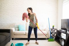 Funny woman using mop as microphone and singing. Beautiful young woman in protective gloves is singing using a mop and smiling while cleaning her house Royalty Free Stock Images