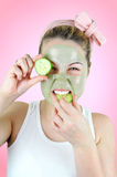 Funny woman wearing green facial mask biting into a slice of cucumber. Royalty Free Stock Images
