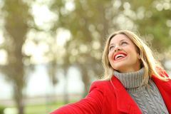 Funny woman joking in a park in winter. Funny woman wearing a red jacket joking in a park in winter Royalty Free Stock Photo