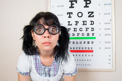 Funny woman wearing spectacles in an office at the doctor Stock Photos