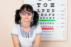 Funny woman wearing spectacles in an office at the doctor Stock Photo