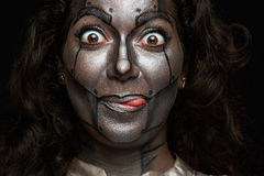 Funny women face. Funny woman face with body art of metal mask on black background Stock Image