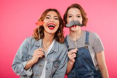 Funny women friends holding fake lips and moustache. Photo of two funny women friends standing isolated over pink background. Looking camera holding fake lips Royalty Free Stock Photos