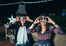 Funny women holding smartphones showing male eyes. Funny young women holding smartphones showing male eyes in the screen on a outdoors party Stock Photos