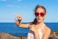 Funny wondering girl holding an atlantic crab on ocean coast. Funny wondering glad teenage girl in red sunglasses holding an atlantic crab on ocean coast. Blue Stock Photography