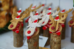 Funny wooden moose deers with red noses and Santa hats Stock Photos