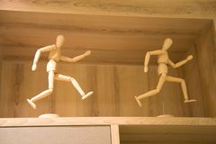 Funny wooden statuette. Wooden puppet Decorative wood on the nBookshelf royalty free stock photos