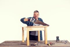 Funny worker in blue shirt working with wood stock photo