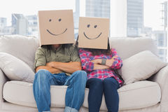 Funny workers with arms crossed wearing boxes on their heads Stock Photography