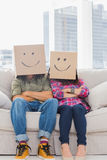 Funny workers with arms folded wearing boxes on their heads Stock Photography