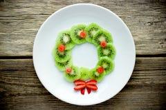 Funny xmas food idea for kids - kiwi strawberry edible Christmas wreath. On a white plate stock photos