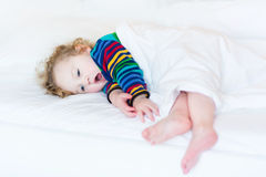 Funny yawning toddler girl taking nap in white bed Royalty Free Stock Photography
