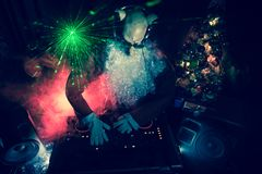 Dj Santa Claus at Christmas with glasses and snow mix on New Year's Eve event in the rays of light stock image