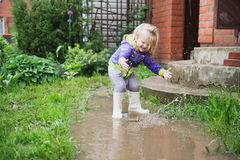 Funny 2 years old baby girl playing in puddle. Stock Photo