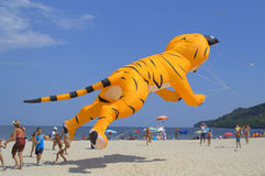 Funny yellow cat kite on the beach. People fun with big jumping yellow cat kite on the beach during the 3rd edition of International Festival of Kites,Varna Stock Image
