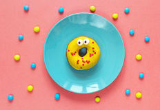 Funny yellow donut with eyes on a blue plate. Stock Photography