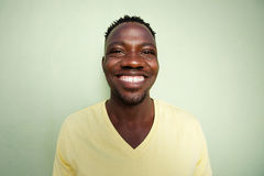 Funny young african man smiling against green wall Royalty Free Stock Photos