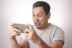 Funny Young Asian Guy Playing Games on Tablet royalty free stock photos