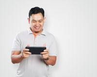 Funny Young Asian Guy Playing Games on Tablet Royalty Free Stock Image