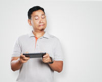 Funny Young Asian Guy Playing Games on Tablet Stock Photos