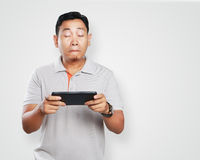 Funny Young Asian Guy Playing Games on Tablet. Photo image portrait of a cute handsome young Asian man with funny face playing games on tablet Stock Photo