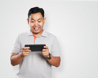 Funny Young Asian Guy Playing Games on Tablet Royalty Free Stock Photography