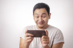 Funny Young Asian Guy Playing Games on Tablet Smart Phone royalty free stock image