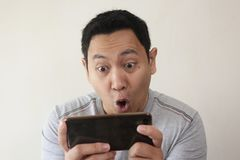 Funny Young Asian Guy Playing Games on Tablet Smart Phone royalty free stock photography