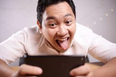 Funny Young Asian Guy Playing Games on Tablet Smart Phone royalty free stock photos