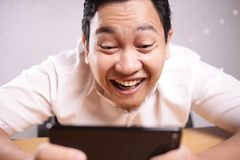 Funny Young Asian Guy Playing Games on Tablet Smart Phone stock photography