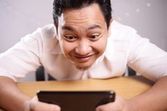 Funny Young Asian Guy Playing Games on Tablet Smart Phone stock photo