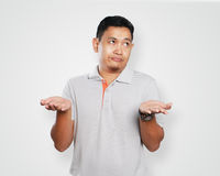Funny Young Asian Guy Showing Unhappy Face. Photo image portrait of a cute handsome young Asian man showing unhappy face, looking to the side with both of his Stock Images