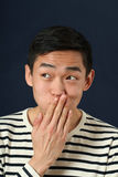 Funny young Asian man covering his mouth by palm Stock Photos